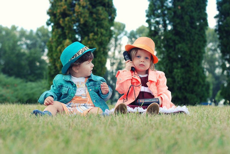 Two kids sitting in the grass dressed from the past