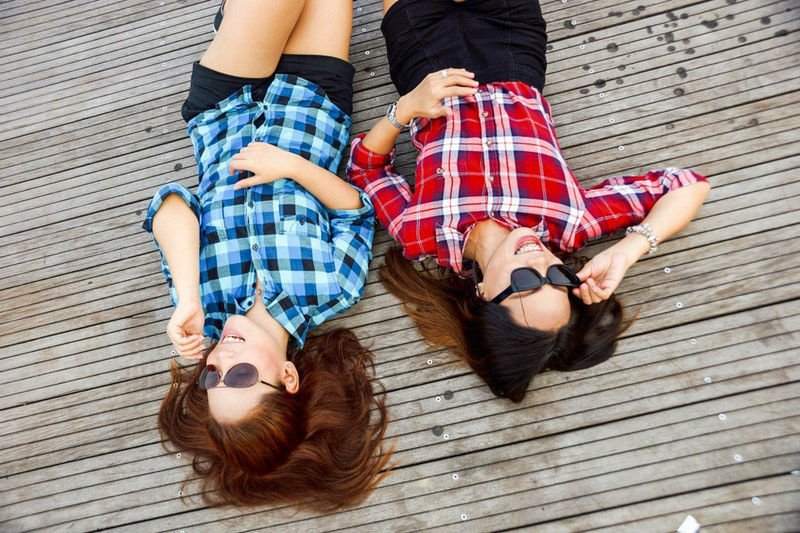 Two girls lying on a deck in the sun