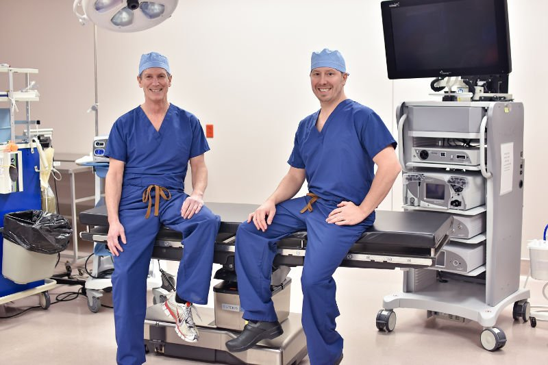 Male doctors sitting on operating room table